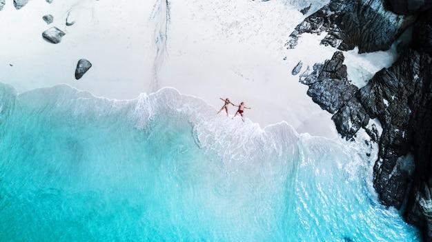 Spiaggia drone vista isola tropicale, spiaggia bianca con onde, coppia sdraiata sulla spiaggia Foto Premium