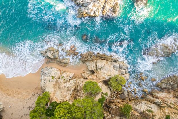 Spiaggia piena di rocce e onde in spagna Foto Premium