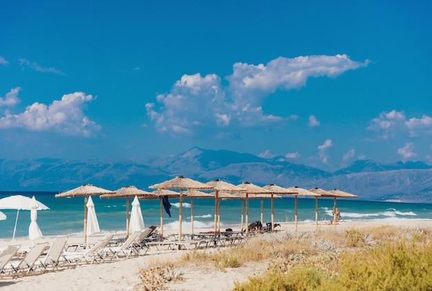 Spiaggia sabbiosa del mare con molti lettini e ombrelloni di paglia Foto Premium