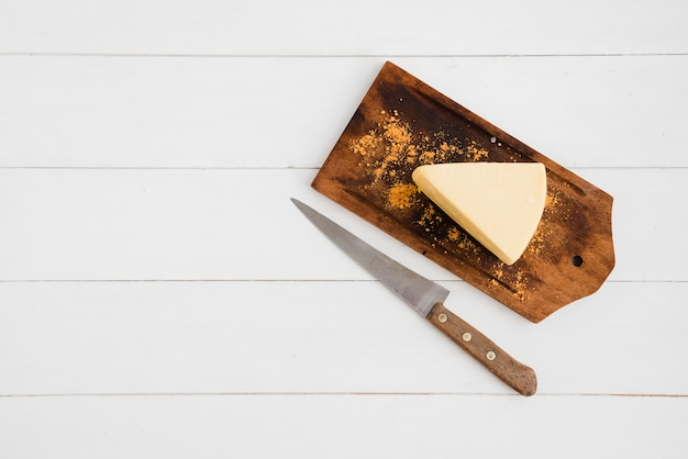 Spicchi di formaggio spolverati di spezie sul tagliere con un coltello affilato sopra il tavolo bianco Foto Gratuite