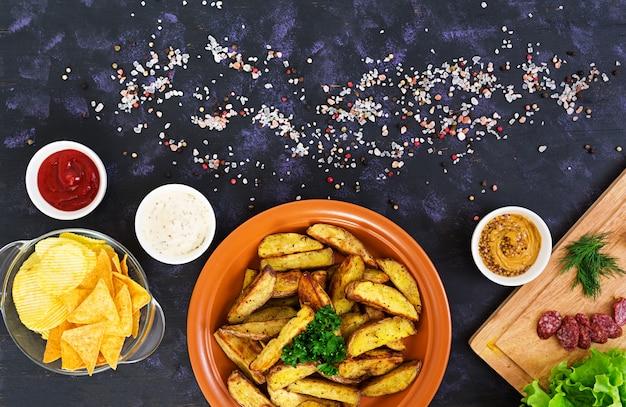 Spicchi di patate al forno con salsicce e spezie. Foto Premium