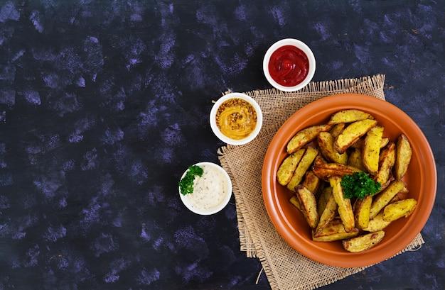 Spicchi di patate al forno con spezie. Foto Premium