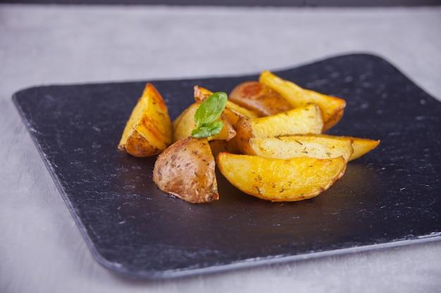 Spicchi di patate al forno fatti in casa con erbe su sfondo nero Foto Premium