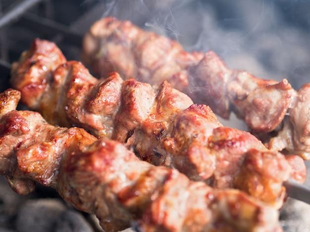 Spiedini di carne alla griglia alla brace, con fumo. il cibo di strada. Foto Premium