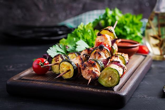 Spiedini di carne alla griglia, spiedini di pollo con zucchine, pomodori e cipolle rosse Foto Gratuite