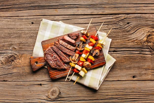 Spiedo di carne e fetta di bistecca fritta sul tagliere di legno Foto Gratuite