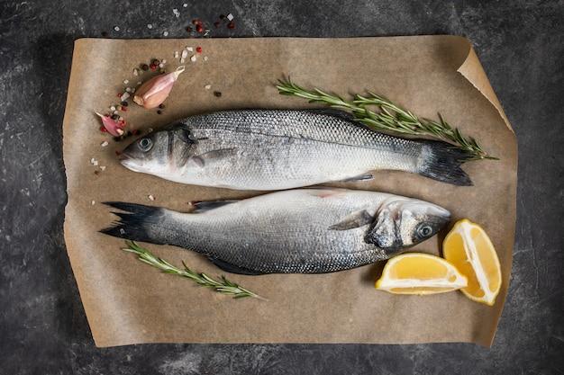 Spigola di pesce fresco e ingredienti per cucinare, limone e rosmarino. vista dall'alto di sfondo scuro. Foto Premium