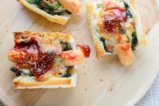 Spinaci al forno con formaggio, salsiccia su baguette, pane francese Foto Premium
