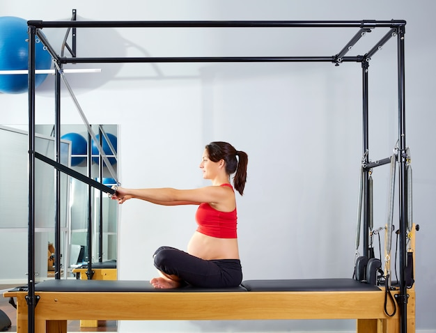 Spinta in avanti del riformatore dei pilates della donna incinta Foto Premium