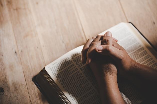 Spiritualità e religione, mani giunte in preghiera su una sacra bibbia in concetto di chiesa per fede. Foto Gratuite