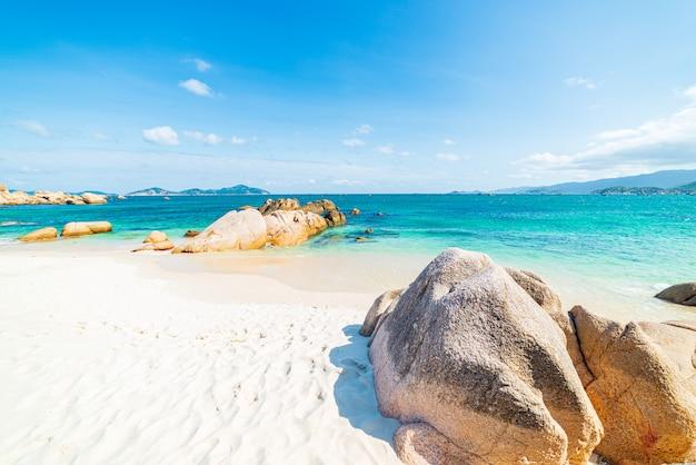 Splendida spiaggia tropicale turchese trasparente acqua massi di roccia unici, cam ranh nha trang vietnam costa sud-est destinazione di viaggio, cielo blu chiaro Foto Premium