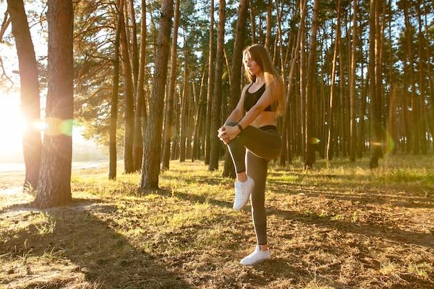 Splendido corridore femminile facendo esercizio di stretching, allenamento nel bosco al sole Foto Gratuite