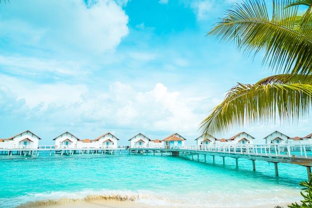 Splendido hotel resort tropicale e isola delle maldive con spiaggia e mare Foto Premium
