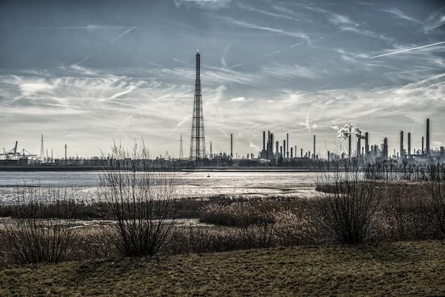 Splendido scenario di edifici industriali sulla riva circondato da erba sotto un cielo mozzafiato Foto Gratuite