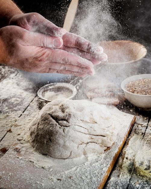Spolverare a mano con la farina sulla pasta sopra il tavolo Foto Gratuite