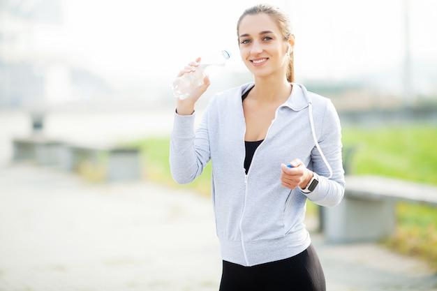 Sport all'aria aperta. donna allegra in acqua potabile delle cuffie Foto Premium