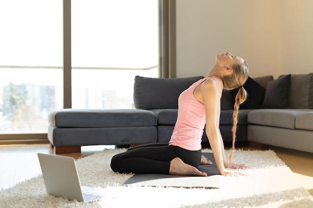 Sport online. giovane donna che fa le esercitazioni sulla stuoia di yoga di fronte al computer portatile Foto Premium