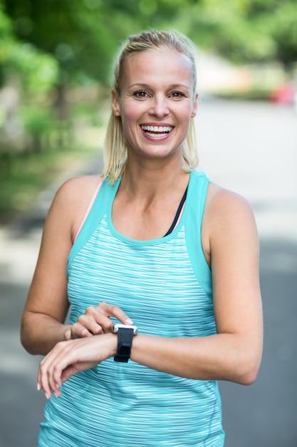 Sportiva che controlla il suo orologio di frequenza cardiaca Foto Premium
