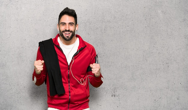 Sportivo bello che celebra una vittoria nella posizione del vincitore sopra la parete strutturata Foto Premium