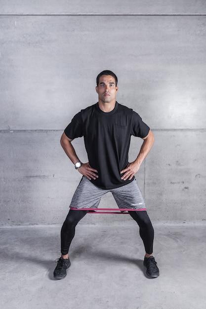 Sportivo che si esercita con elastico sulle gambe Foto Premium
