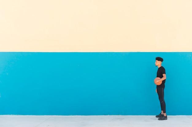 Sportivo etnico in abito nero in piedi con il basket Foto Gratuite