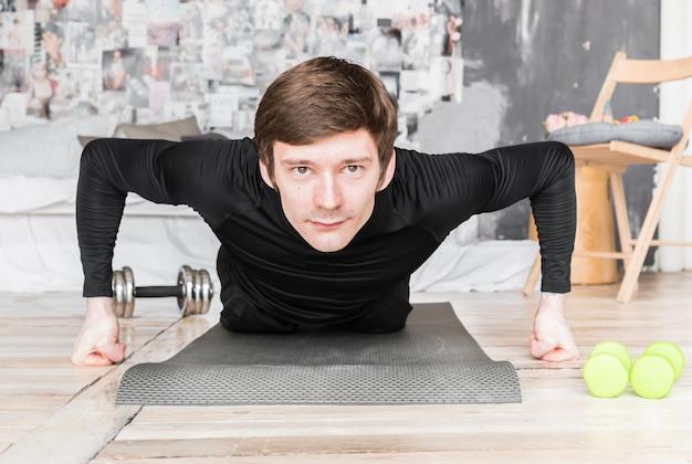 Sportivo facendo flessioni sul tappetino Foto Gratuite