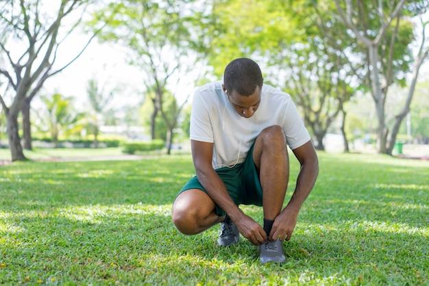 Sportivo nero si prepara per la mattina che si esercita nel parco. Foto Gratuite