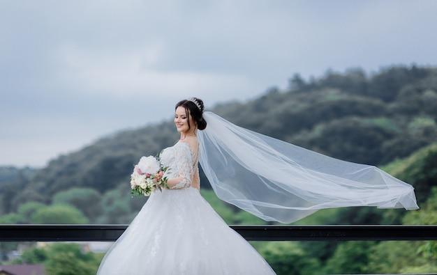 Sposa abbastanza caucasica sorrisa con il velo lungo all'aperto che tiene il mazzo di nozze Foto Gratuite