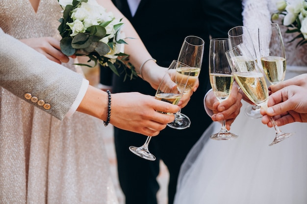 Sposa con lo sposo che beve champagne sul loro matrimonio Foto Gratuite