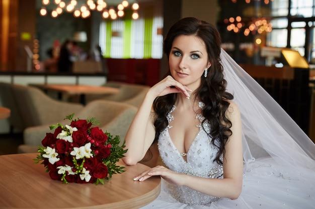 Sposa con un mazzo di fiori seduti al tavolo Foto Premium