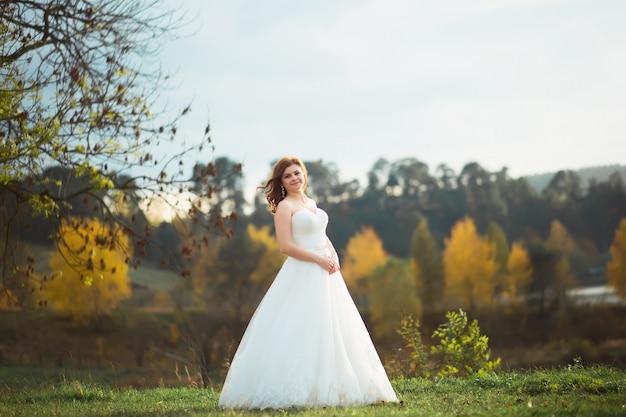Sposa di bellezza in abito da sposa con velo bouquet e pizzo sulla natura. ragazza bellissima modella in un abito da sposa bianco. ritratto femminile nel parco. donna con acconciatura. signora carina all'aperto Foto Premium