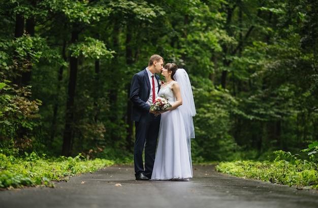 Sposa e sposo al giorno delle nozze, camminando all'aperto in estate sulla natura. Foto Gratuite