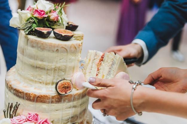 Sposa e sposo che tagliano la torta nuziale decorata con frutta, macarons e fiori di fico Foto Premium