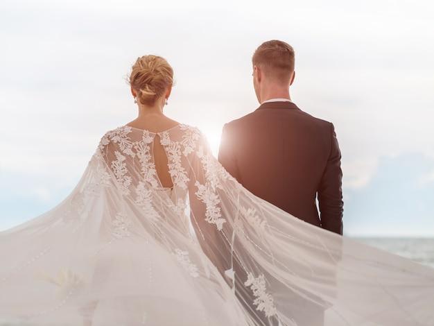 Sposa e sposo sulla spiaggia con un momento romantico Foto Premium