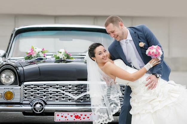Sposa e sposo sulla strada vicino alla macchina retrò Foto Premium