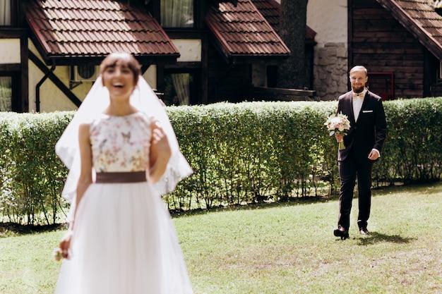 Sposa felice di sorriso che aspetta lo sposo con il mazzo del fiore Foto Premium