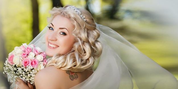 Sposa felice in un velo che tiene il suo mazzo che esamina macchina fotografica nella campagna Foto Premium