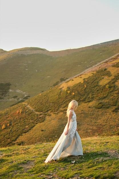 Sposa in abito da sposa vintage correndo via tramonto spettacolare paesaggio montano in background Foto Premium