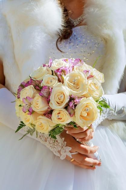 Sposa in abito firmato tenendo un bouquet di rose. Foto Premium