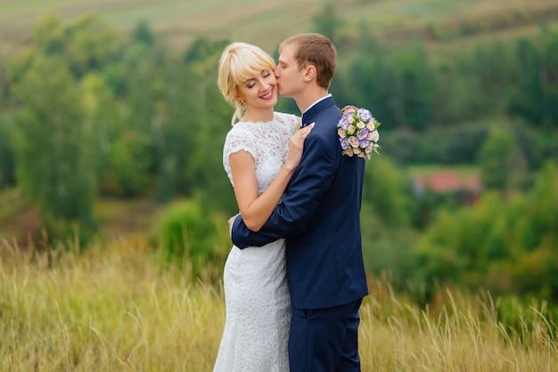 Sposi all'aperto in posizione natura. sposi in amore al giorno delle nozze. Foto Gratuite