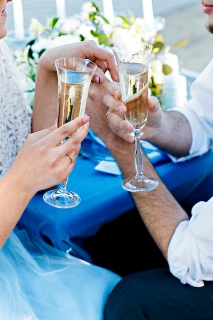 Sposi con gli occhiali. cerimonia matrimoniale. il bouquet della sposa sposa e sposo con anelli. sposi novelli con bicchieri di spumante Foto Premium