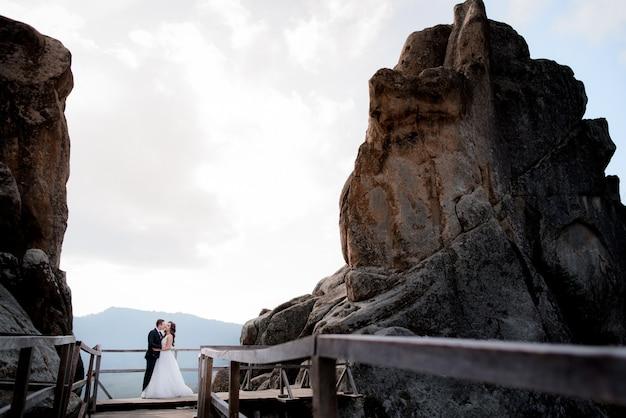 Sposi è in piedi sul ponte di legno tra due alte scogliere e baci, avventura di matrimonio Foto Gratuite
