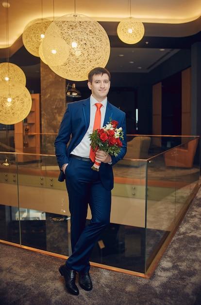 Sposo con un bellissimo mazzo di fiori in attesa della sua sposa Foto Premium