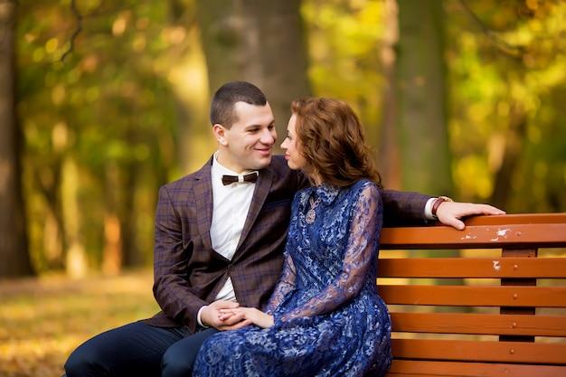 Sposo e sposa che si siedono sul banco in un parco. sorriso abito da sposa. Foto Premium
