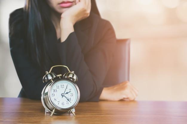 Sprecare il concetto di tempo con la donna d'affari annoiato in attesa di qualcuno in ritardo Foto Premium