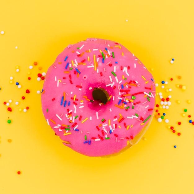 Spruzza su ciambella rosa su sfondo giallo Foto Gratuite