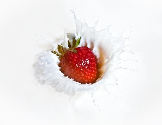 Spruzzata della fragola nell'immagine di macro del latte Foto Premium