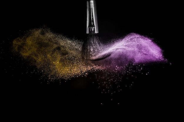 Spruzzata di polvere d'oro e viola a sfondo nero Foto Premium