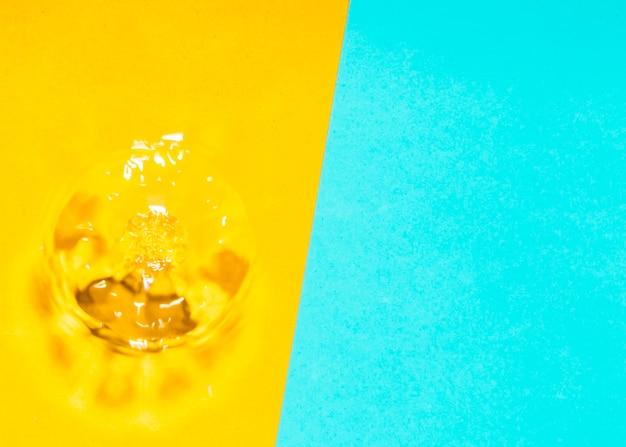 Spruzzata e bolle dell'acqua su fondo giallo e blu Foto Gratuite