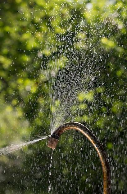 Spruzzi d'acqua dal vecchio rubinetto arrugginito e che è tappo chiuso Foto Premium